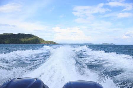 spatten golfwater van speedbootmotoren op zee- en eilandachtergrond