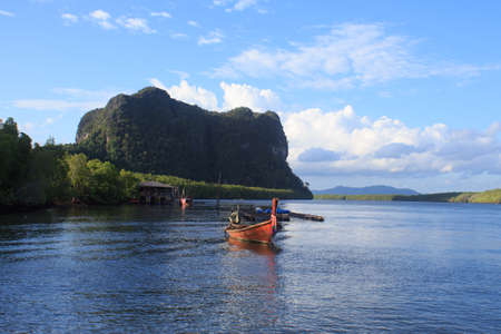 reflect: wooden rowing boat on blue sea water and sun light reflect, nature landscape  at Trang Thailand Stock Photo