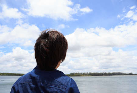 backview: back of young man wear jeans shirt looking and thinking over blue sea sky backview