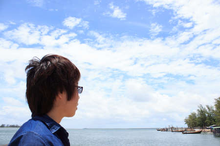 backview: back of young man wear glasses, shirt jeans looking and thinking over sea backview