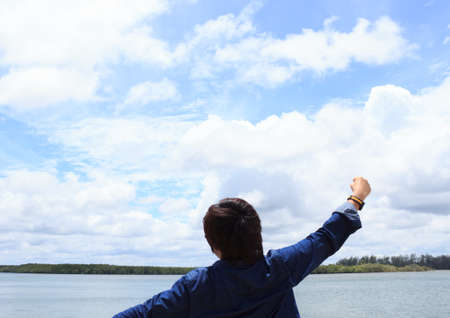 arms wide open: back of young man wear shirt jeans and arms wide open in front of sea Stock Photo
