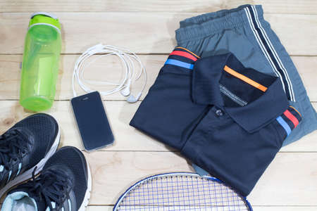 sportswear and earphones mobile-phone lifestyle flat lay overhead view. bottle,sportswear,sneakers and badminton racket on wooden background Stock Photo