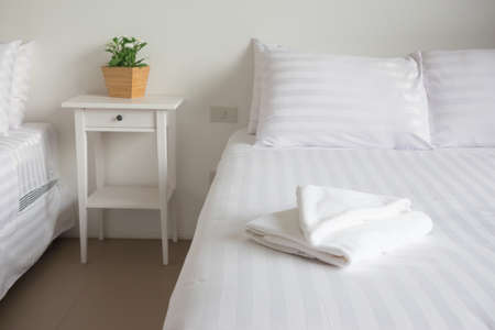 king size: white king size bed, two pillows, towel and tree pot plant in bedroom for rest and relax, feel comfortable