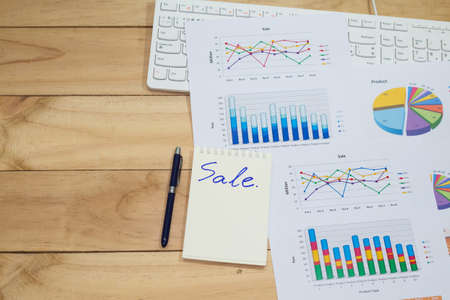 business performance: Sale analysis report show result success charts and graphs on document paperwork with blank space wooden table background