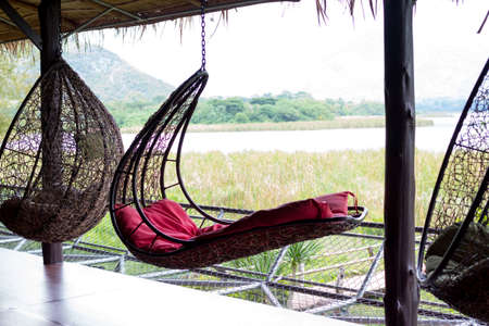 rattan oval hanging chair with red pillow in tropical plant