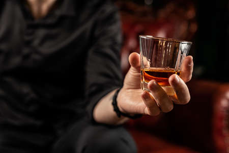 Male hand holds a glass of elite alcohol, in a black shirt, close-up, studio light Reklamní fotografie