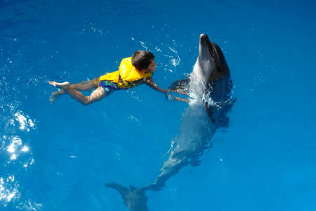 clinging: A happy child with a dolphin in a life jacket, holding on to fins, in the Sevastopol Dolphinarium