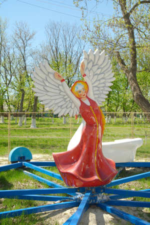 The statue of a girl in a long Russian folk sarafan dress hands like wings open and on the head kokoshnik in the form of a big star stands in the center of the childrens carousel.