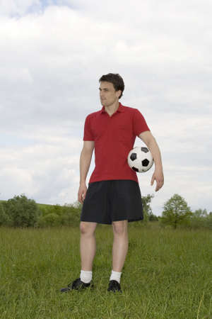 socker: man playing football outside for recreation Stock Photo