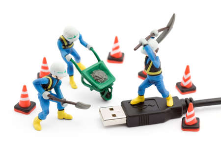 miniature people: computer repair concept - usb cable repaired by workers isolated Stock Photo
