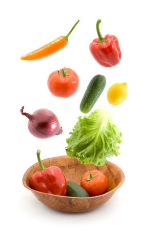 vegetables falling into dish studio isolated Stock Photo
