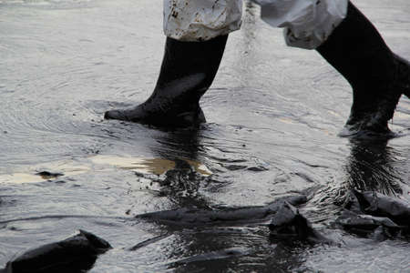 oil spill: Close Up of workers legs with boots due to accident from crude oil spill.