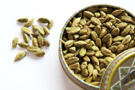indian cookery: A bunch of Iranian Cardamon pod seeds treads in a metal bowl  Isolated on white background Stock Photo