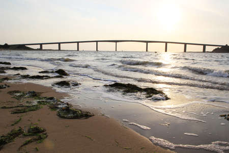 vendee: A beach on late afternoon and a bridge of Noirmoutier between mainland and a small island in Vendee in France