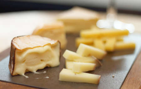 tabla de quesos: Tabla de quesos con trozos de tipos Vaus de queso servido en una mesa a la luz casi natural de un restaurante Foto de archivo