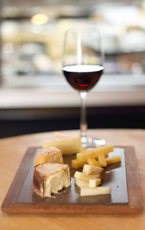 tabla de quesos: Tabla de quesos con trozos de tipos Vaus de queso y un vaso de vino tinto sobre un fondo sirve en una mesa a la luz casi natural de un restaurante Foto de archivo
