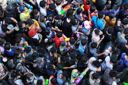 silom: Bangkok, THAILAND - April  15,2016 :A lot of Foreign tourists and Thai people enjoy splashing water and put the natural white powder on their faces and mix with water during Songkran Festival on Silom Road Editorial