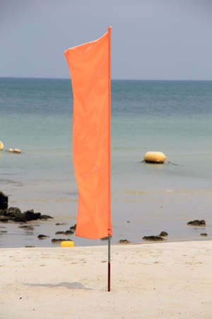 Play it Safe, Beach warning flag flapping in the wind, It is reccomended not to go in the water under red flag conditions. Banco de Imagens