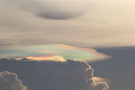 Colorful iridescent pileus clouds or rainbow clouds in the late evening