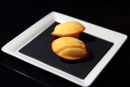 Madeleine cookies on isolated black background
