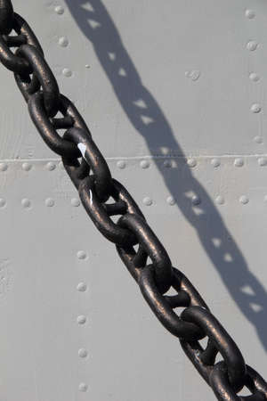 Wet and rusted big chain of steam punk submarine or military ship at the metal background with rivets