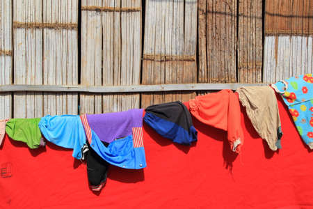 Joyful Karen Hill Tribe Style Summer Laundry. Colorful cloths on a laundry line and bamboo wall back ground, Countryside scene. Reklamní fotografie
