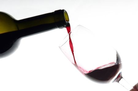 redwine: Wine poured from a bottle in to a glass.