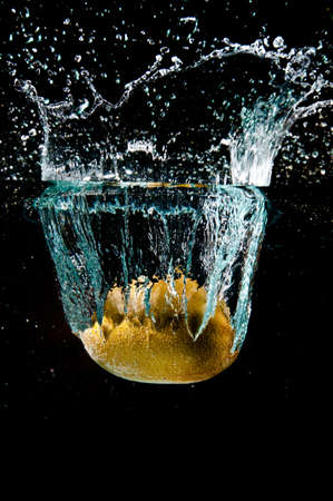 fruit drop: kiwi fruit drop into water with splash on black background