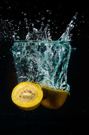 kiwi fruta: kiwi cortado en el agua con el chapoteo sobre fondo negro