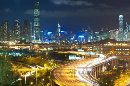 highway with traffic in blur motion and city skyscapper background photo