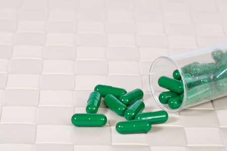 green pill and transparent bottle photo