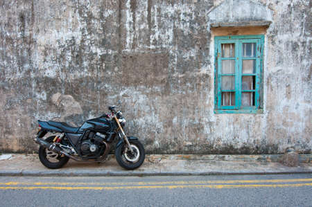 vintage wall and window and a modern motor cycle photo