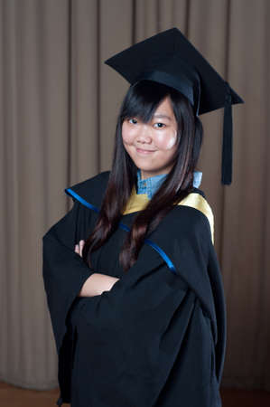 confident graduate asian girl student in front of curtain photo