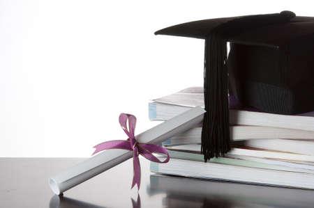 birrete de graduacion: Certificado de Posgrado y la tapa de postgrado en una pila de libros aislados en blanco Foto de archivo