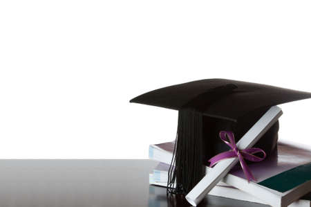 cap and gown: graduate certificate and graduate cap on a stack of books isolated on white Stock Photo