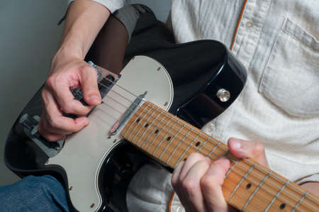 man hand playing electronic guitar photo