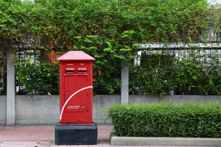 Red postbox on footpath bangbox thailand photo