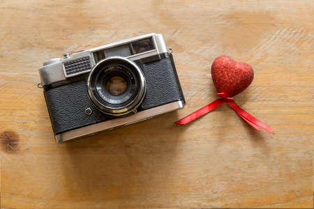 Retro Camera with red hearts on a wooden background Stock Photo