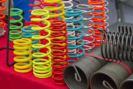 Coil springs are many colors on the red table. 免版税图像