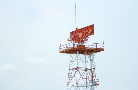 Red-and-white airport radar in daylight