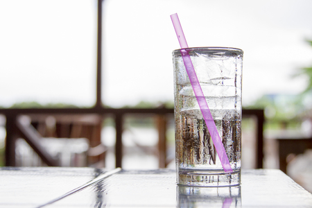 cold: Ice glass placed on a wooden desk. With a pink tube