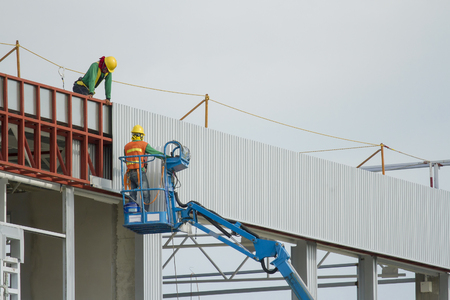 Workers in a baskets are installing sheet, building a factory. Stock Photo