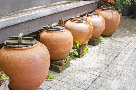 earthenware: Five ancient orange jars are arranged together.