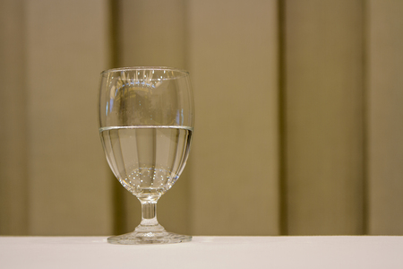 Water glass with brown background.