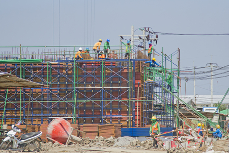 Workers in a baskets are installing sheet, building a factory. Editorial