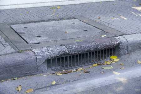 Water drainage old on the way and fallen leaves Stock Photo