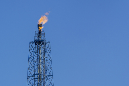 Gas flares in petroleum refinery  with blue sky background