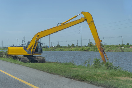 Yellow backhoe working riverside and on the roadside