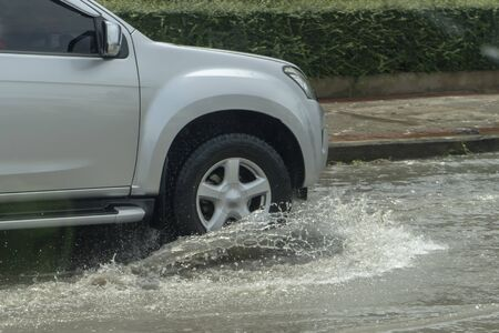 Truck driving through flood water on the road