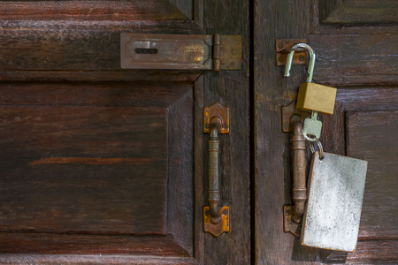 Old rusty and key locks on wooden door Stock Photo